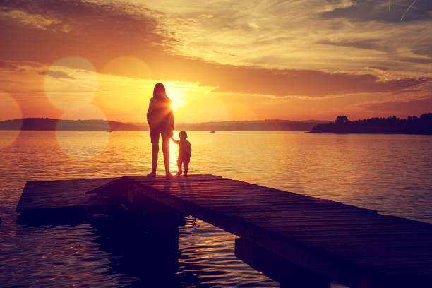 Silhouettes of Mother and Her Son by the Lake – Foto