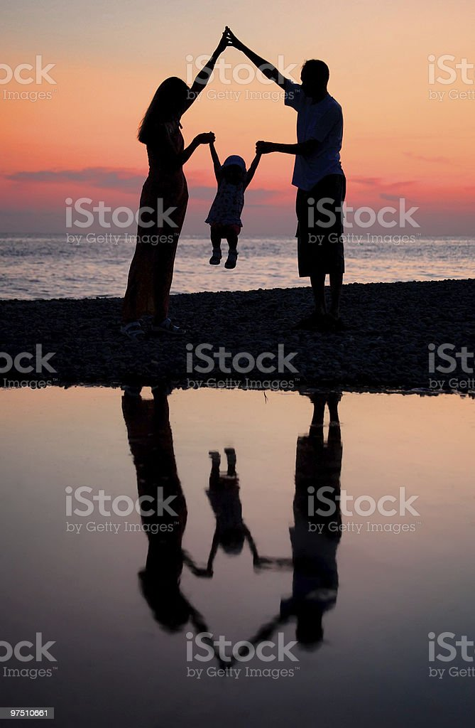 Silhouettes of parents with child royalty-free stock photo