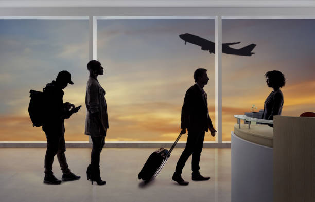 Silhouettes of Passengers in Line at Airport stock photo