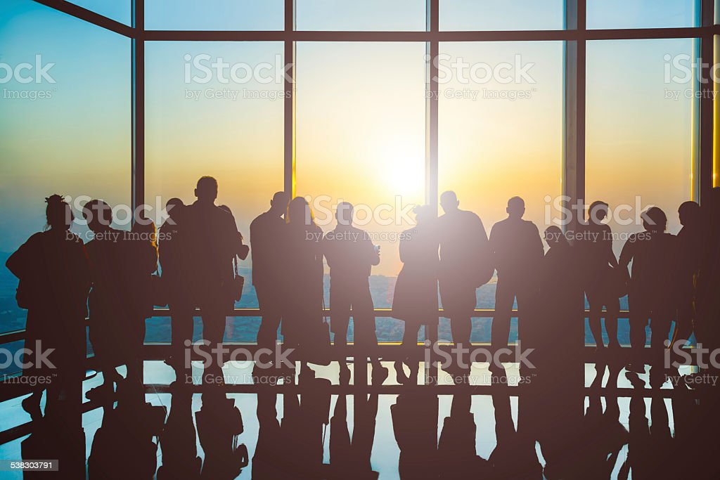 Silhouettes of people at sunset stock photo