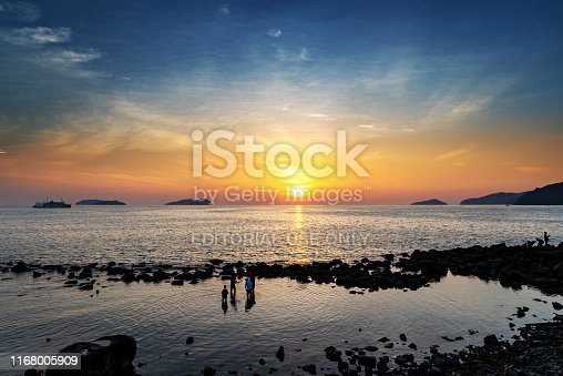 Kota Kinabalu, Malaysia - August 13, 2019:Silhouettes of people at the beach during sunset, Kota Kinabalu, Sabah, Malaysia.