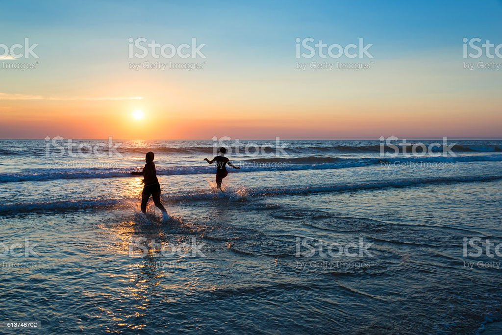 Silhouettes of people enjoying the sunset on the atlantic ocean stock photo