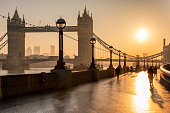 The iconic Tower Bridge in London, UK, during sunrise and silhouettes of people going to their work