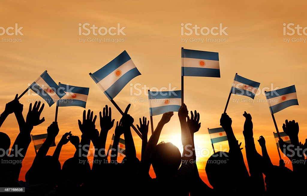Silhouettes of People Holding Flag of Argentina stock photo