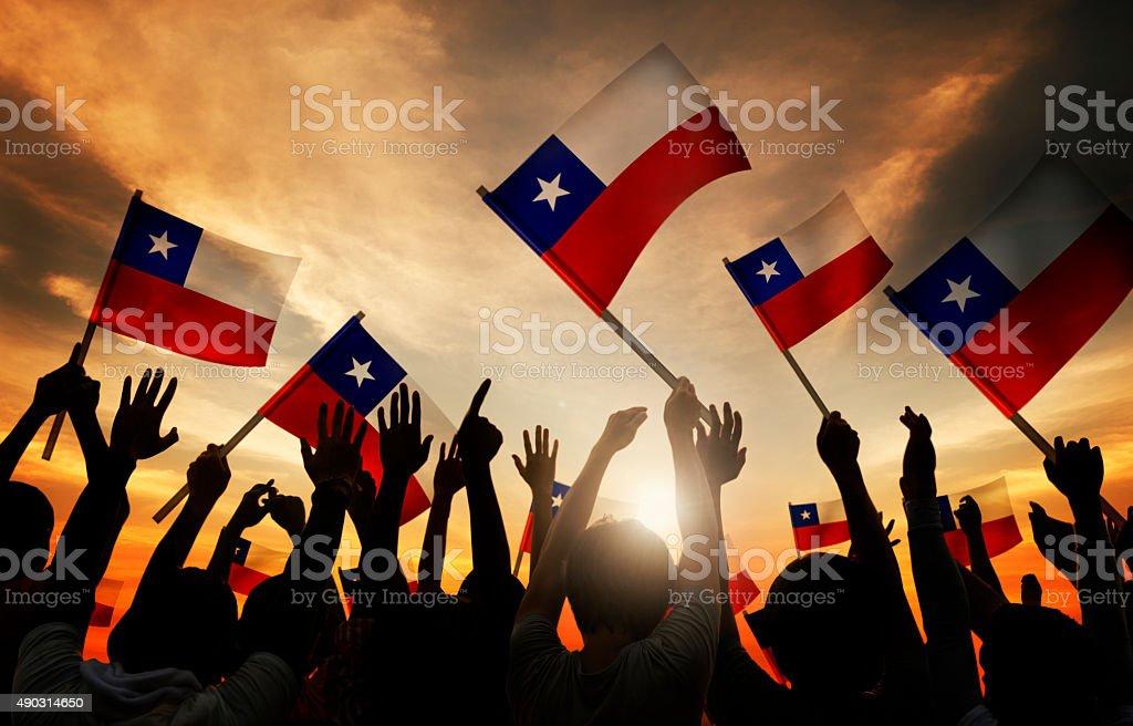 Silhuetas de pessoas segurando Bandeira do Chile - foto de acervo