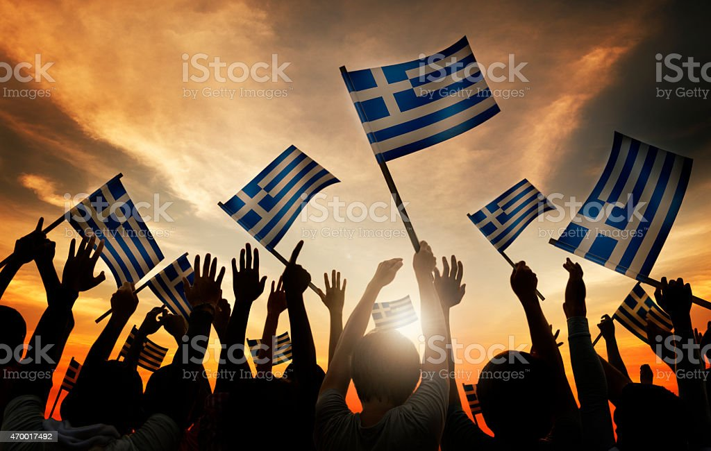 Silhouettes of People Holding Flag of Greece stock photo