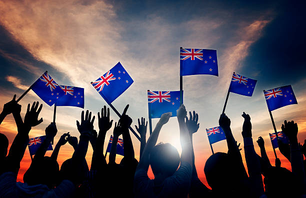 silhouettes of people holding flag of new zealand - new zealand flag stock photos and pictures