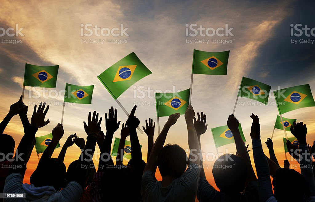 Silhouettes of People Holding the Flag of Brazil stock photo