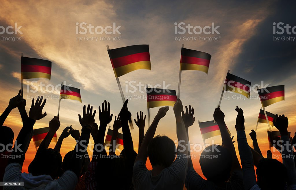 Silhouettes of People Holding the Flag of Germany stock photo