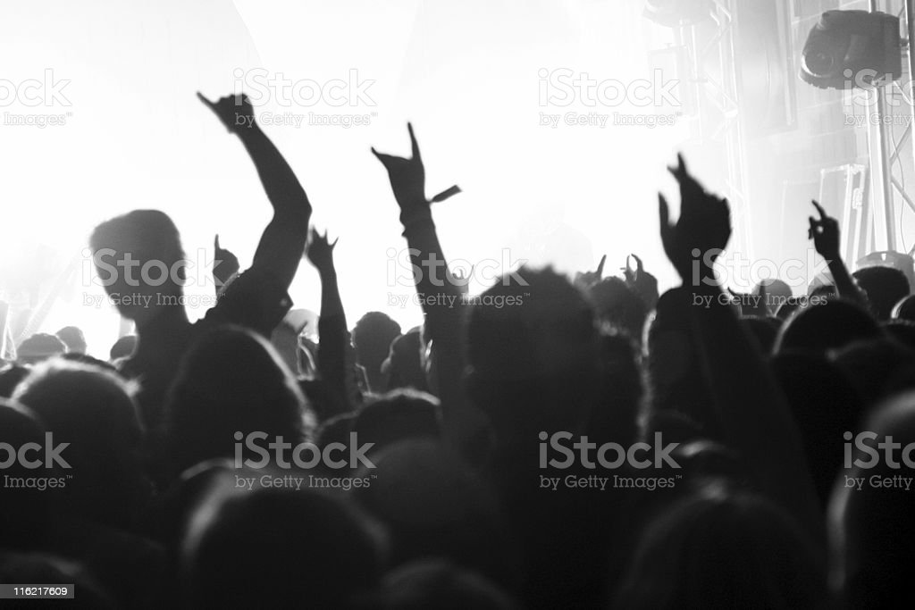 Silhouettes of people in a crowd with a bright stage stock photo