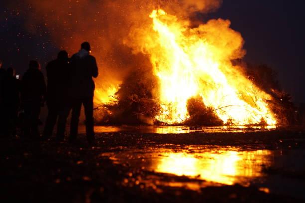 silhouetten von menschen vor osterfeuer - osterfeuer stock-fotos und bilder