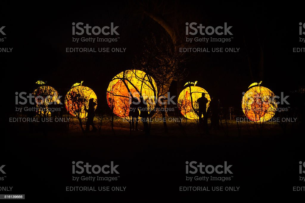 Silhouettes of people in front of orange lanterns installation stock photo