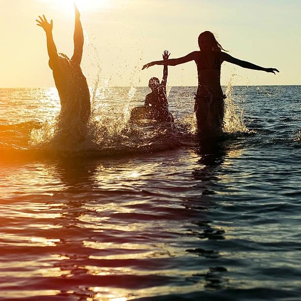 Silhouetten von Menschen im Ozean springen – Foto