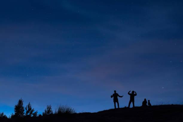 silhouetten von menschen auf einem hügel unter dem sternenhimmel - neue abenteuer stock-fotos und bilder