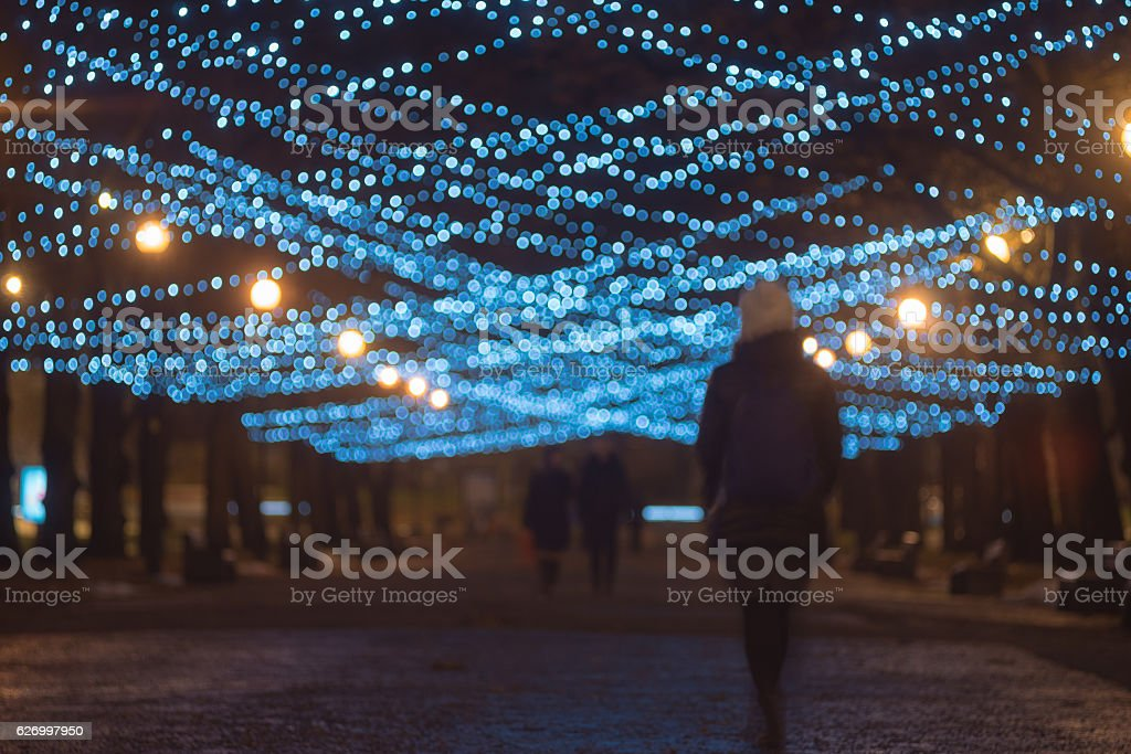 Silhouettes of people on festive illuminated alley – Foto