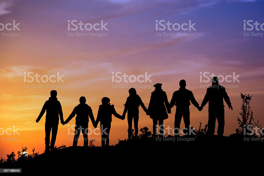 silhouettes of people on mountains stock photo