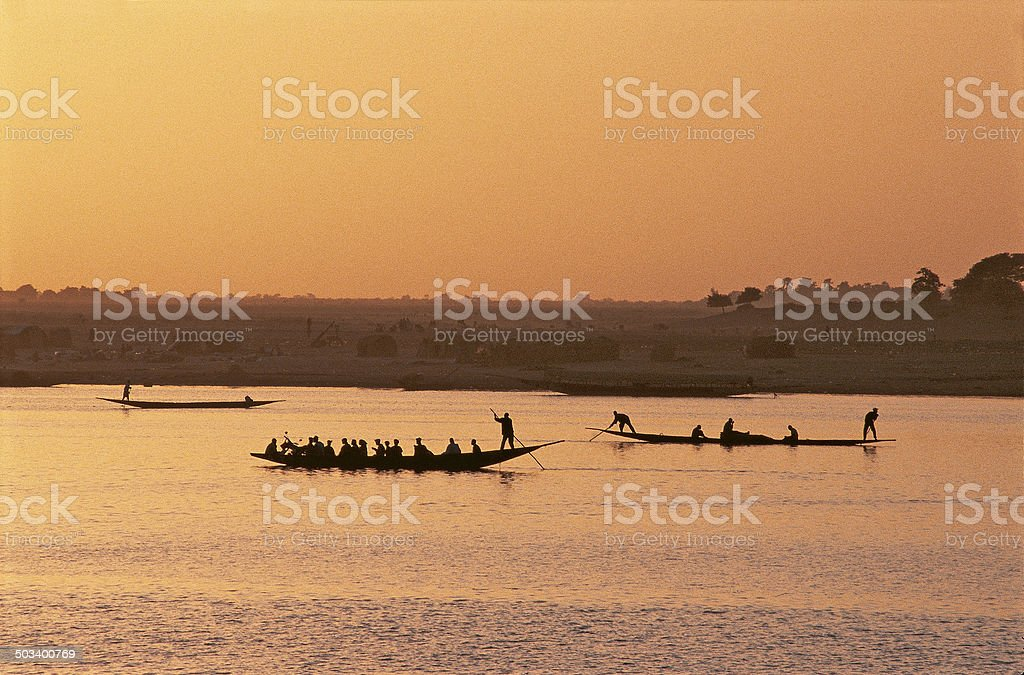 Silhouettes of people on Niger river stock photo