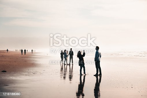 San Francisco, USA - January 26, 2020: Silhouettes of happy people enjoying on Ocean Beach in winter. Famous tourist destination. Romantic sunny view of wet sand and tide. Amazing panorama. Seaside