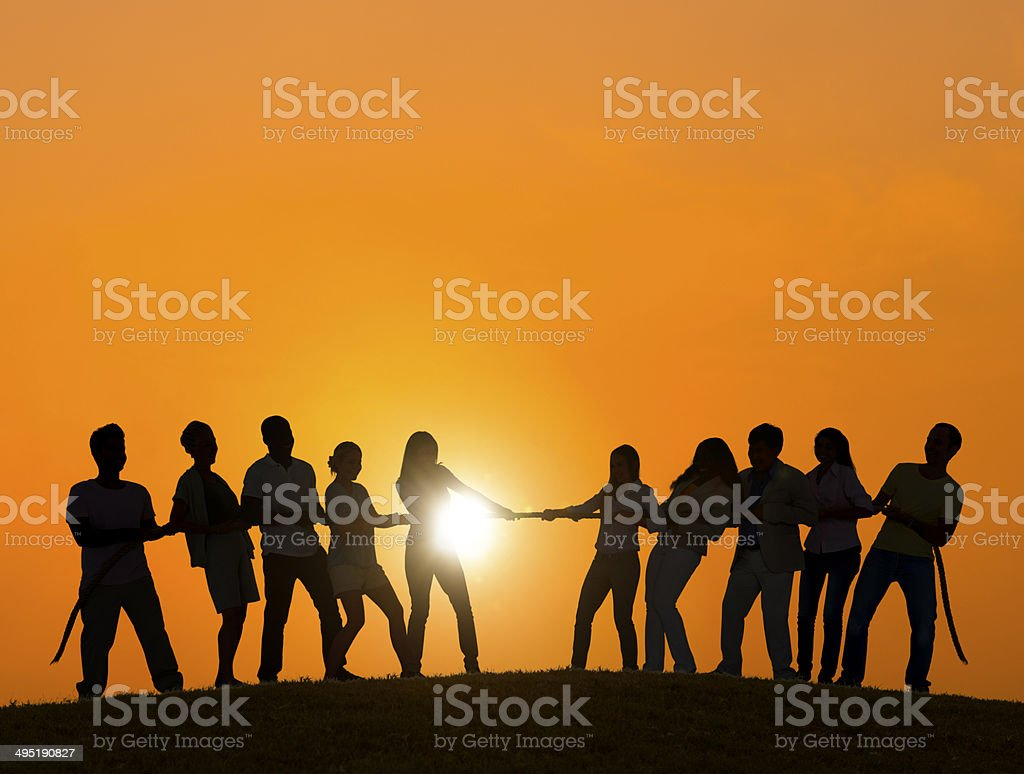 Silhouettes of People Playing Tug of War stock photo