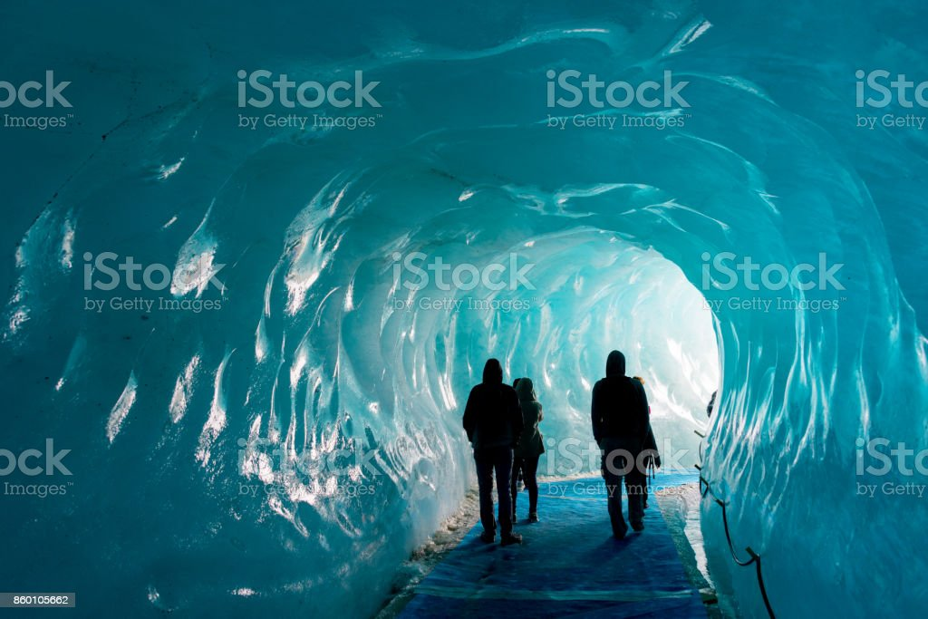 Silhouettes of people visiting thee ice cave of the Mer de Glace glacier,  in Chamonix Mont Blanc Massif, The Alps, France stock photo