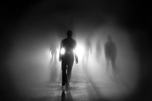 Silhouettes of people walking into light