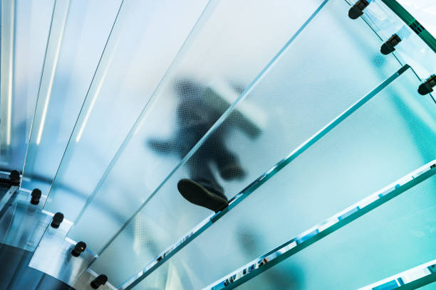 Silhouettes of people walking on a glass spiral staircase – Foto