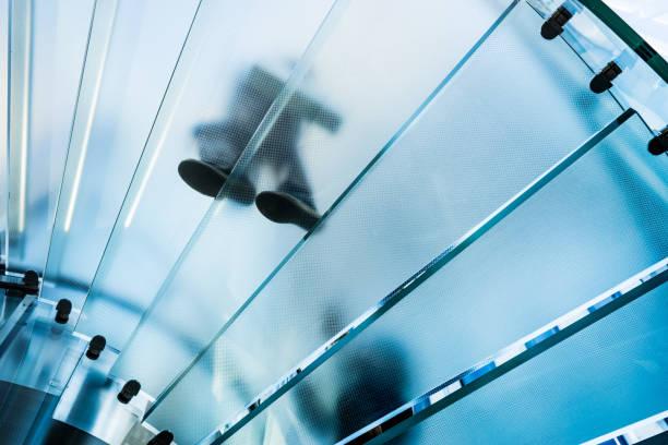 Silhouetten von Menschen zu Fuß auf eine Glas-Wendeltreppe – Foto
