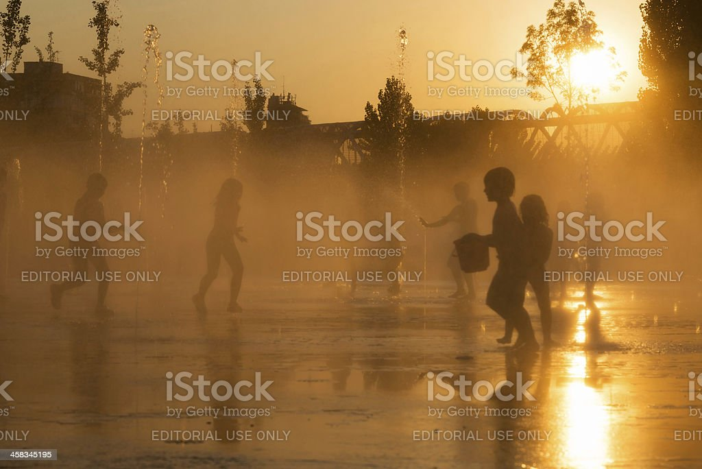 Silhouettes of playful children in a fountain in Madrid stock photo