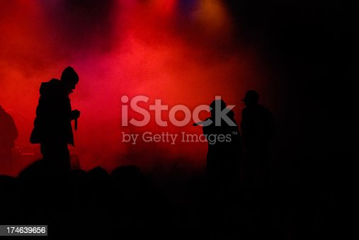 hip hop concert with rapper on stage. red enlightened fog in the background. silhouette of three rappers. little bit of noise in the fog due to high iso