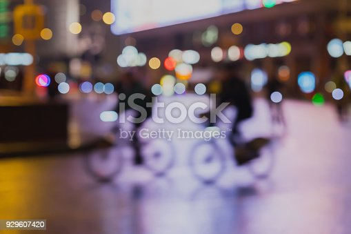 929609038istockphoto Silhouettes of riding Cyclists in traffic on night city, light bokeh, abstract, motion blur, violet background 929607420