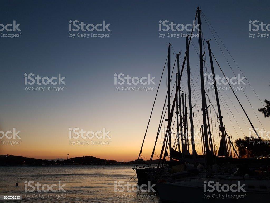 silhouettes of sail poles at sun set stock photo