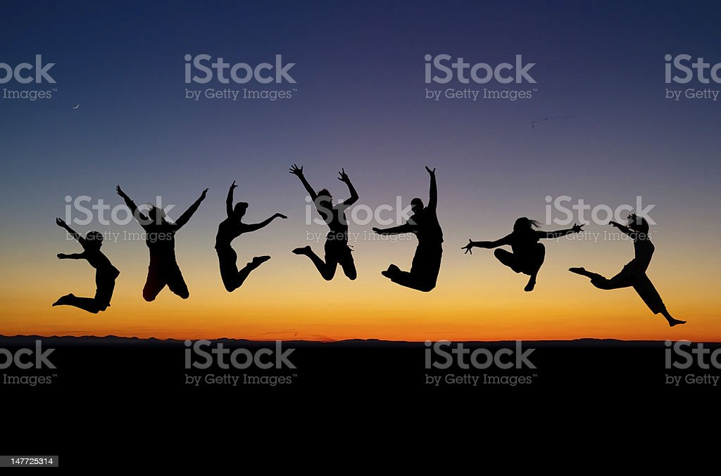 Silhouettes of seven people jumping against sunset  stock photo