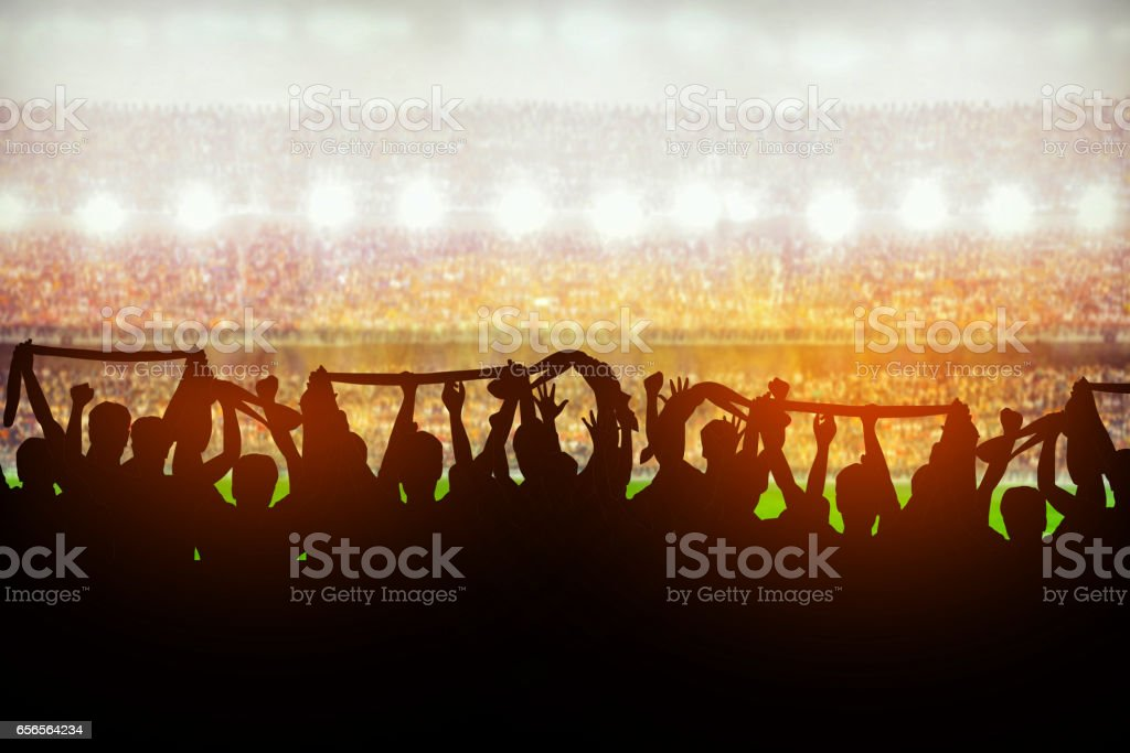 Silhouettes of soccer or rugby supporters in the stadium during match stock photo