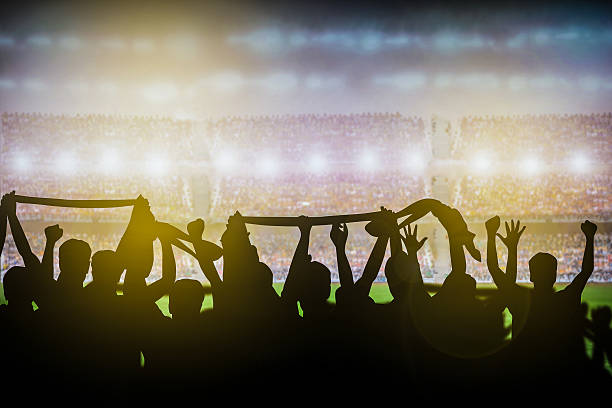 Silhouettes of soccer or rugby supporters in the stadium - Photo