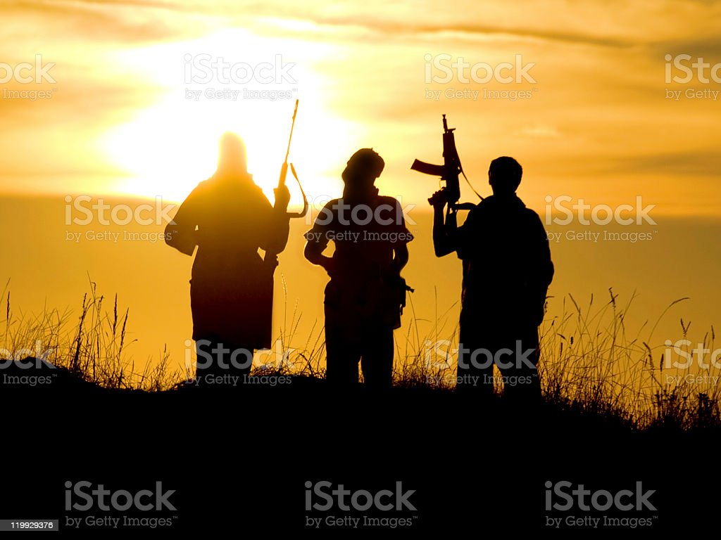 Silhouettes of soldiers against a sunset royalty-free stock photo