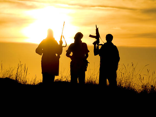 Silhouettes of soldiers against a sunset Silhouettes of several soldiers with rifles against a sunset terrorism stock pictures, royalty-free photos & images