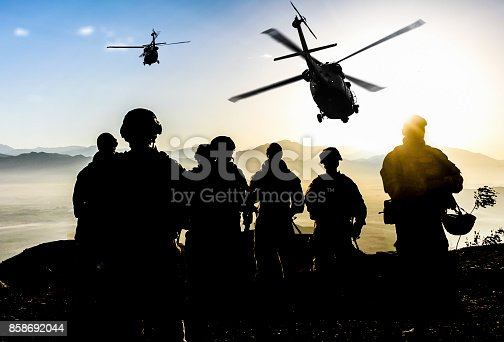istock Silhouettes of soldiers during Military Mission at dusk 858692044