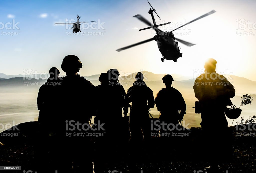 Silhouettes of soldiers during Military Mission at dusk stock photo
