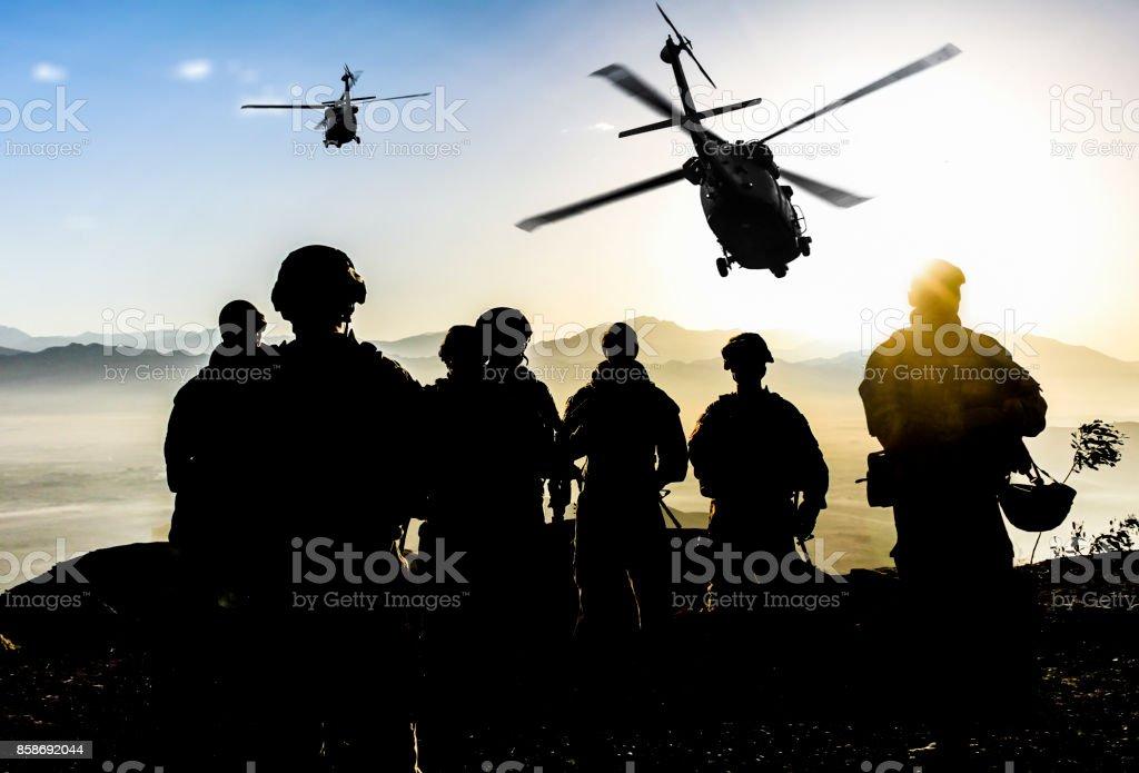 Silhuetas dos soldados durante uma missão militar ao entardecer - foto de acervo