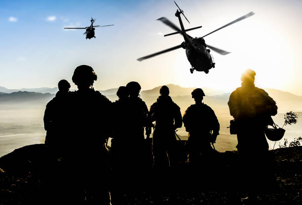 silhouettes of soldiers during military mission at dusk - armed forces stock photos and pictures