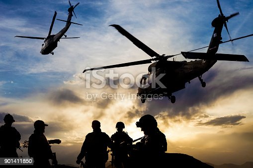 istock Silhouettes of soldiers during Military Mission at dusk 901411850