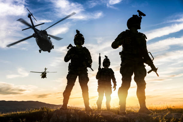 Silhouettes of soldiers during Military Mission at sunset Squad of Three Fully Equipped and Armed Soldiers Standing on Hill  at sunset armed forces stock pictures, royalty-free photos & images