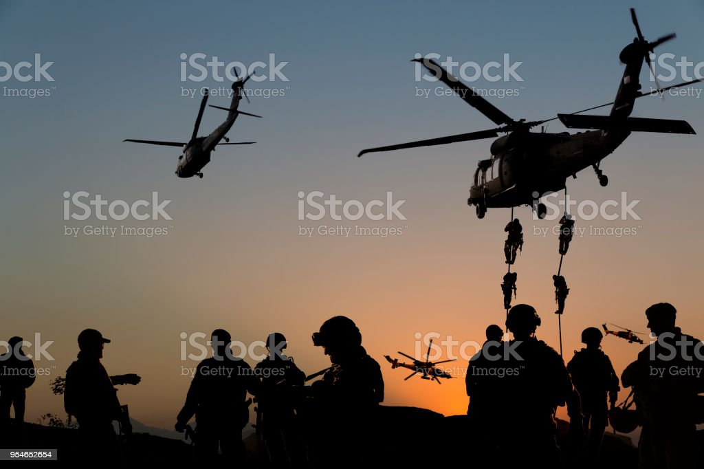 Silhouettes of soldiers on Military Mission at dusk ATTENTION FOR INSPECTOR: This is a composite image and some models were used multiple times in the photo. There are 13 people on the photo, but actually there were just 6 models on the shoot. That's why, I uploaded 6 model release. Please consider this.    Silhouettes of soldiers on Military Mission at dusk Adult Stock Photo