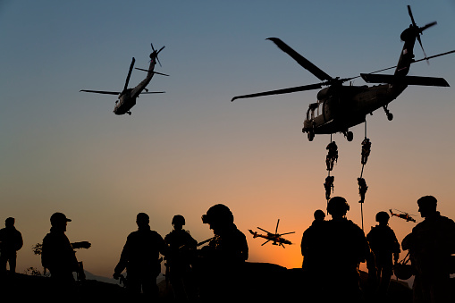 Silhouettes Of Soldiers On Military Mission At Dusk Stock Photo - Download Image Now
