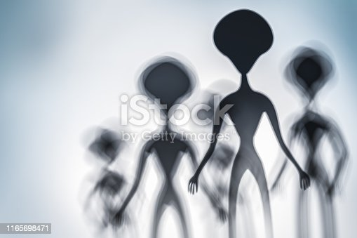 istock Silhouettes of spooky aliens and bright light on behind them 1165698471