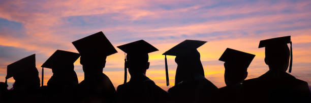Silhouettes of students with graduate caps in a row on sunset background. Graduation ceremony at university web banner. Silhouettes of students with graduate caps in a row on sunset background. Graduation ceremony at university web banner. university stock pictures, royalty-free photos & images