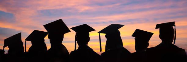 Silhouetten von Studenten mit Graduiertenkappen in einer Reihe auf Sonnenuntergang Hintergrund. Abschlussfeier auf Universitäts-Web-Banner. – Foto