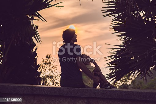497142294 istock photo Silhouettes of the father and son, who meet the sunset in the tropics against the backdrop of palm trees 1212138909