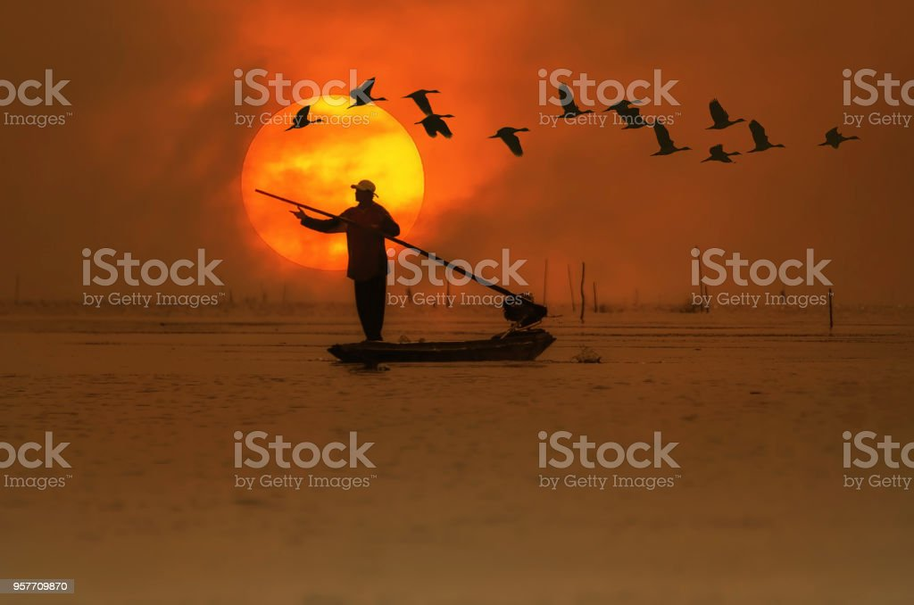 Silhouettes of the traditional stilt fishermen at sunset. stock photo
