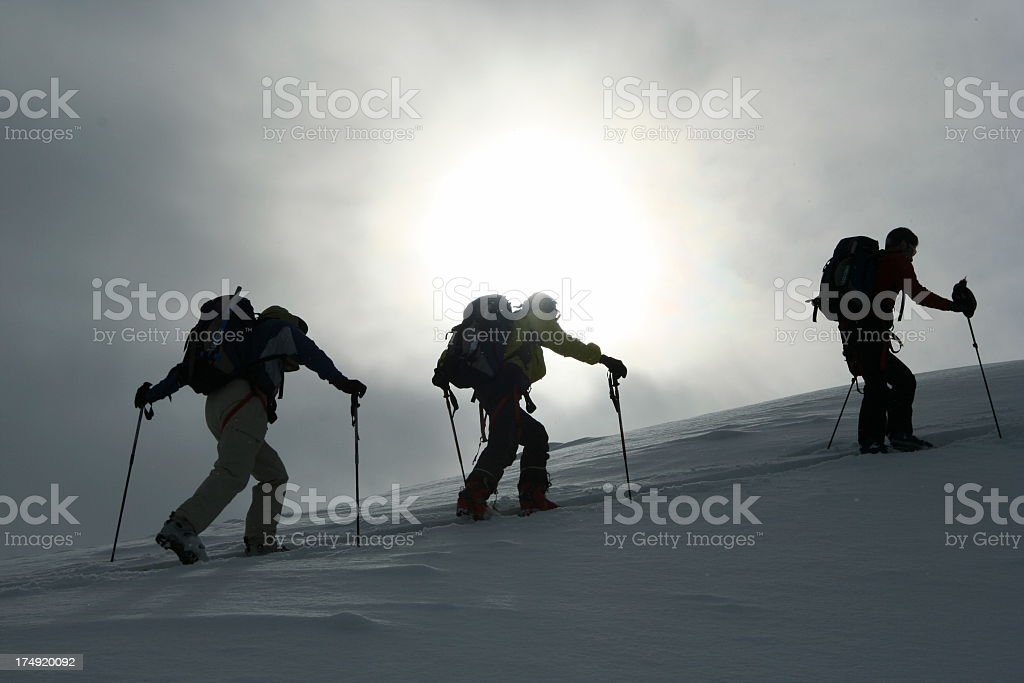 Silhouettes of three cross-country skiers climbing a ridge royalty-free stock photo